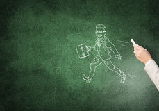 Caricatures of happy businessman. Female hand drawing with chalk walking businessman on blackboard Royalty Free Stock Photo