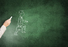 Caricatures of walking businessman. Female hand drawing with chalk thinking businessman on blackboard stock photography