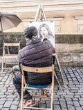 Caricaturist drawing female portrait Stock Photos