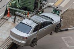 Carichi che del camion di rimorchio l'automobile per la violazione del parcheggio governa difficoltà Fotografia Stock