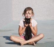 Caricia de la chica joven con el gatito Imagen de archivo libre de regalías
