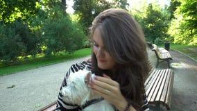 Caricia hermosa de la mujer su perro casero precioso sentarse en banco en parque Tiro del PDA almacen de metraje de vídeo
