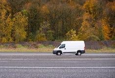 Carico commerciale e furgone di piccola impresa mini che va sulla strada w fotografia stock libera da diritti