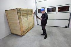 Carico - consegna, lavoratore che controlla grande scatola di legno con la compressa Fotografia Stock