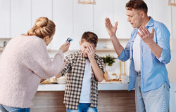 Carign parents punishing his son in the kitchen Royalty Free Stock Photography