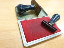 Carimbo de borracha que encontra-se na tabela de madeira fotografia de stock royalty free