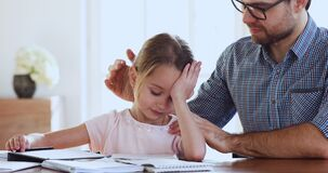 Caring dad support encourage sad tired child daughter studying together
