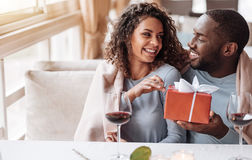 Caring African American man giving the present to his girlfriend. For all my love to you. Loving smiling happy African American men sitting in the restaurant and Stock Photos