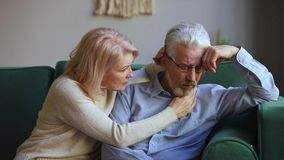Caring aged wife comforting talking to upset elderly husband. Caring understanding middle aged wife embracing comforting talking to upset grey haired elderly stock video footage
