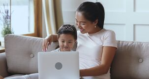 Asian mother teaching kid daughter using laptop for children education