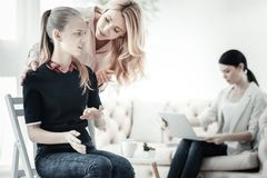Caring attentive woman standing and talking to girl. Let me help. Caring attentive cute women standing near a girl talking and tilting to her Royalty Free Stock Photos