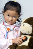 Caring for Bear. A young girl cares for her sick bear royalty free stock images