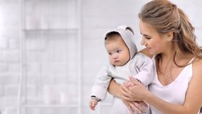 Caring beautiful young mother hugging and kissing little son having love feeling medium close-up. Smiling family attractive woman with cute baby enjoying stock video footage