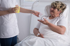 Caring about bedridden woman. Young nurse caring about bedridden elder woman stock photography