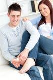 Caring boyfriend massaging his girlfriend's feet Stock Photos