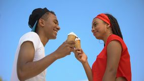 Caring boyfriend wiping nose of cute girlfriend eating big ice-cream, proximity. Stock footage stock video footage