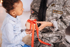 Caring bright girl presenting a gift. I wrapped it myself. Amazing energetic sweet child giving her mom a secret box greeting her upon her arrival while she stock photo
