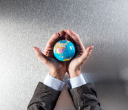 Caring businessman protecting the future of planet for environment health. Caring businessman protecting the future of the planet, holding the earth within his royalty free stock images