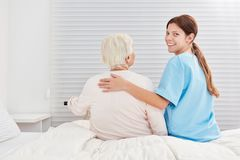 Caring care help helps senior citizen out of bed. Caring ng assistant helps senior citizen out of bed royalty free stock photography