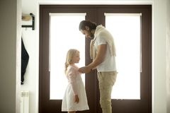 Caring dad dressing buttoning little daughter at home, good fath. Caring dad gets daughter ready for school or walk standing at entrance door home hall, loving Stock Photos