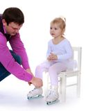 Caring dad helping skates her little adorable Stock Photos