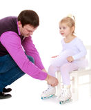 Caring dad helps put skates her little daughter Royalty Free Stock Photos