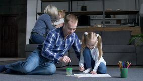 Caring dad with preteen daughter painting at home stock footage