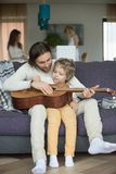 Caring dad teaching kid son to play guitar at home. Caring dad teaching kid to play guitar at home, loving father holding musical instrument strumming with boy royalty free stock photos