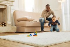 Caring daddy teaching his son walking. First steps. Loving young smiling afro-american father teaching his little bay walking and helping him while sitting on royalty free stock image