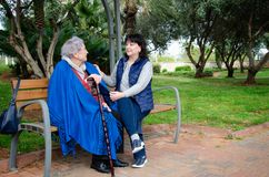 Caring daughter and elderly mother are sitting on a park bench. Daughter and mother or caregiver and old lady just walked in the park and sat down to rest on the royalty free stock images