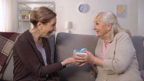Caring daughter giving giftbox to mother, making surprise to mothers day, b-day. Stock footage stock video footage