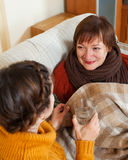 Caring daughter giving the glass of water to  mature mother Royalty Free Stock Images