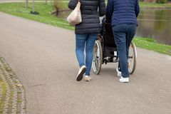 Caring daughter wheelchair walking green nature nurse walk stroller old person retired stock photos
