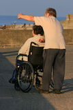 Caring for the Disabled. Woman in a wheelchair with a man pointing something out to her in the distance Stock Photography