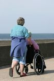 Caring for the Disabled. Elderly woman pushing a man in a wheelchair on a seaside promenade. Sea (out of focus) to the rear Stock Images