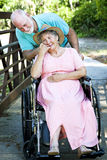 Caring for Disabled Wife. Senior man caring for his disabled wife in wheelchair Royalty Free Stock Photography
