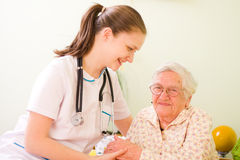 Caring doctor with happy elderly woman stock image