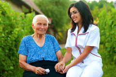 Caring doctor with sick elderly woman outdoors royalty free stock photography