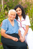 Caring doctor with sick elderly woman outdoors Royalty Free Stock Photos