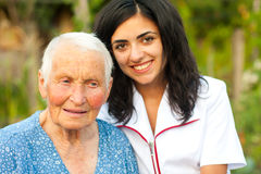 Caring doctor with sick elderly woman outdoors stock photos