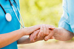 Caring for Elderly. Doctor or nurse holding elderly ladys hands stock photos