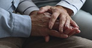 Caring elderly wife holding hand of senior grandpa give empathy