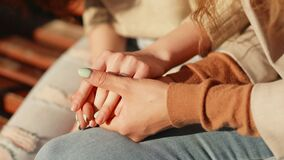 Caring young woman holding hand supporting her friend and give empathy and support. Close up of female hands of two