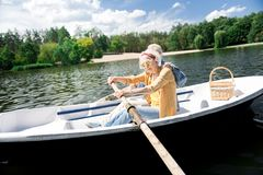 Caring elderly husband helping his wife holding paddle sitting in boat. Helpful wife. Caring elderly husband wearing jeans jacket helping his beautiful stylish stock photos