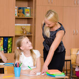 Caring elementary school teacher helping student in classroom Royalty Free Stock Photos
