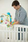 Caring father assembling baby`s cot and putting toy carousel in. Young caring father assembling baby`s cot and putting toy carousel in it Royalty Free Stock Image
