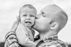 Caring father calms toddler son outdoors Stock Photo