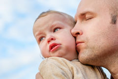 Caring father calms toddler son outdoors Stock Images