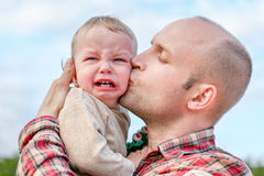 Caring father calms toddler son outdoors Royalty Free Stock Photos