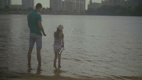 Caring father and cute daughter angling on river stock video footage